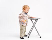 Kid comparing with a stool. Kid comparing his height size with a stool chair royalty free stock photography