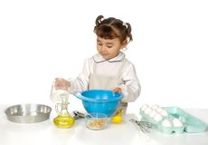 Kid cooking. Cute little girl baking, isolated on white background Royalty Free Stock Photo