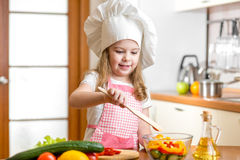 Kid cooking at kitchen. Kid girl cooking at kitchen Royalty Free Stock Images