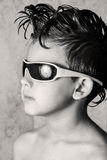 Kid and cool haircut. Boy playing has black glasses on with the cool haircut stock photo