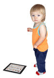 Kid costs about Tablet PC, which lies on the floor. Royalty Free Stock Image