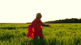 The kid in the costume of a superhero in a red cloak runs along the green lawn against the backdrop of the sunset. Showing the flight of the plane in a slow stock video