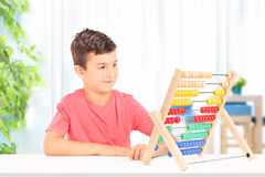 Kid counting with abacus seated on table at home Royalty Free Stock Photography