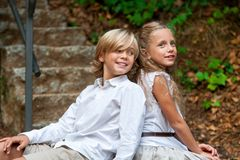 Kid couple sitting together on stairs outdoors. Stock Image