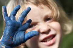 Kid covered in paint. A young child with hand covered in dry blue paint. Very shallow depth of field royalty free stock image