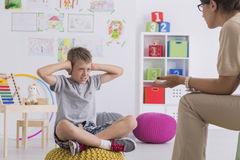 Kid covering his ears during therapy. Angry kid covering his ears during therapy in room full of toys Stock Photos