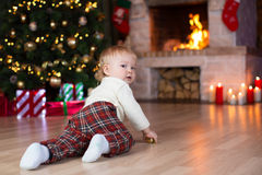 Kid crawling to gifts lying under Christmas tree Stock Photo