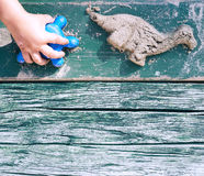 Kid creating animal forms with sand. Copyspace at the bottom of image Royalty Free Stock Photo