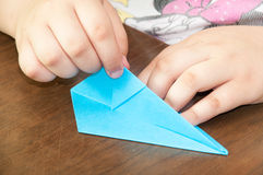 Kid creating origami airplane on the table Royalty Free Stock Image