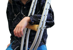 Kid and crutches. Closeup of a kid with crutches over white Royalty Free Stock Photography