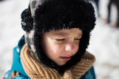 Kid crying after being hit in the face with a snowball Royalty Free Stock Image