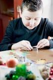 Kid cutting dough Stock Images