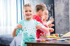 Kid cutting snowflake from paper. Schoolchildren playing with colorful plasticine Stock Photo