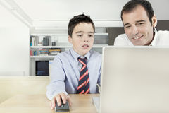 Kid and dad on laptop Stock Images