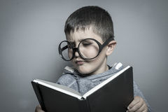 Kid, dark-haired young student reading a funny book, reading and Royalty Free Stock Photos