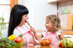 Kid daughter feeding mother vegetables in kitchen. Kid feeding mother vegetables in kitchen stock images