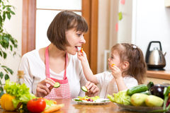 Kid daughter feeding mother vegetables in kitchen Stock Images