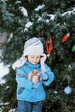 Kid decorate the Christmas tree outdoor in a winter park. Gifts and Christmas trees. Stock Photos
