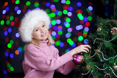 Kid decorating Christmas tree on bright backdrop Royalty Free Stock Photos