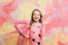 Kid with decorative love heart. Child girl on colorful background. Childhood and happiness. Small girl with love heart. valentines day holiday and party Royalty Free Stock Images