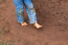 Kid dirty feet on muddy ground. Kid wearing jeans trousers walking on muddy ground Royalty Free Stock Photos