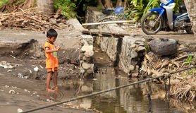 Kid in dirty water. BALI - JANUARY 26. Balinese child playing in dirty water on January 26, 2012 in Bali, Indonesia. According to Asian Development Bank, over Stock Photos