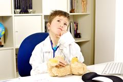 Kid doctor checking up bear plush serious Royalty Free Stock Photo
