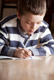 Kid does lessons lying on the floor Royalty Free Stock Photos