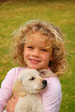 Kid with dog. Outdoor portrait of a beautiful little caucasian girl child smiling, sitting and holding her cute Labrador Retriever dog puppy in the backyard Royalty Free Stock Images
