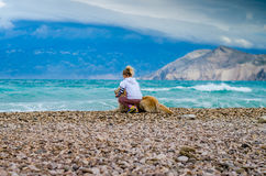 Kid and dog in the beach watching to the sea Stock Image