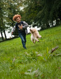 Kid and Dog running. Picture of a young boy (7) and his labradoodle dog running together over a green meadow. The dog is making contact with the kid. Low point Stock Photo