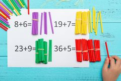 Kid doing addition equations using counting rods. Kid doing some addition equations using counting rods royalty free stock photo