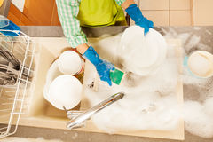 Kid doing the dishes with sponge in foamy sink. Top view picture of kid doing the dishes with sponge in foamy sink in the kitchen royalty free stock images