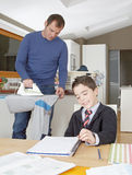 Kid doing homework, dad ironing. Royalty Free Stock Photography