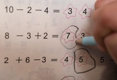 Kid doing homework of simple subtraction & addition Stock Images