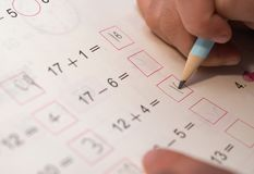 Kid doing homework of simple subtraction & addition Royalty Free Stock Photos