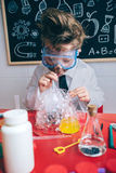 Kid doing soap bubbles with straw in glass royalty free stock images