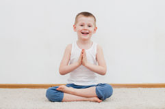 Kid doing yoga relaxing exercise Stock Photos