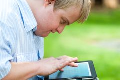 Kid with down syndrome playing on tablet. Stock Photos