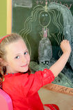Kid drawing. Happy kid,drawing on blackboard in school or home with chalk Stock Photo
