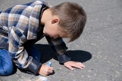 Kid drawing on asphalt in spring, child paint crayons Royalty Free Stock Images
