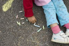 Kid drawing with chalk. Stock Image
