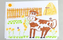 Kid drawing of cute white and brown cow on yard with green grass, stack of hay and wooden fence stock illustration