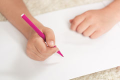 Kid drawing with felt pen on blank paper sheet Royalty Free Stock Photos