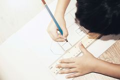 Kid drawing a house. On paper Stock Image