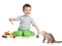 Kid drawing with paints and playing with kitten Royalty Free Stock Images