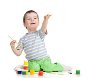 Kid drawing with paints pointing above camera Royalty Free Stock Photos