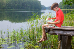 Kid drawing a summer landscape with forest lake sitting on a jet Stock Images