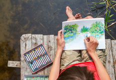 Kid drawing a summer landscape with forest lake sitting on a jet Royalty Free Stock Photography