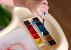 The kid draws a first drawing watercolor. Hand and Brush royalty free stock image